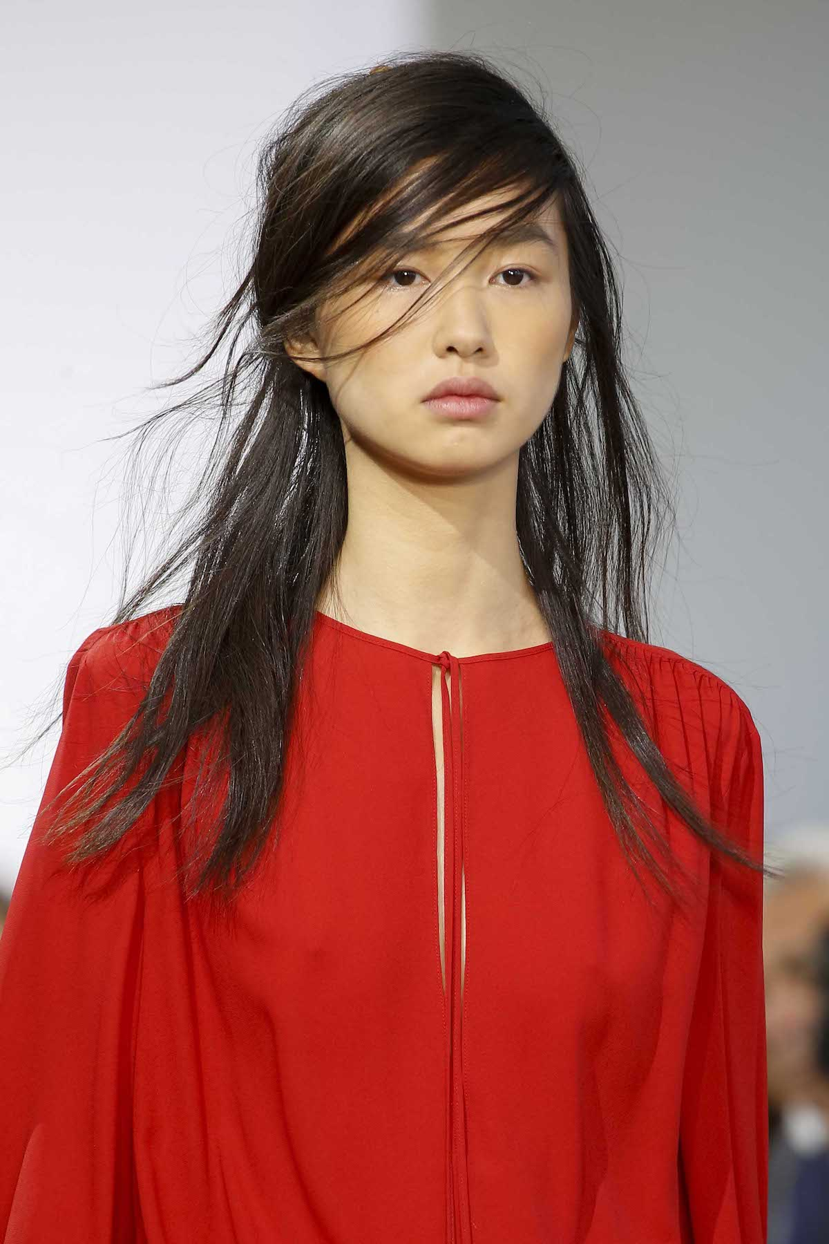 Wanita Asia dengan rambut lurus panjang warna hitam dan poni samping.