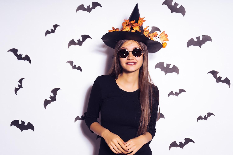 Wanita asia dengan kostum Halloween minimalis dengan topi penyihir