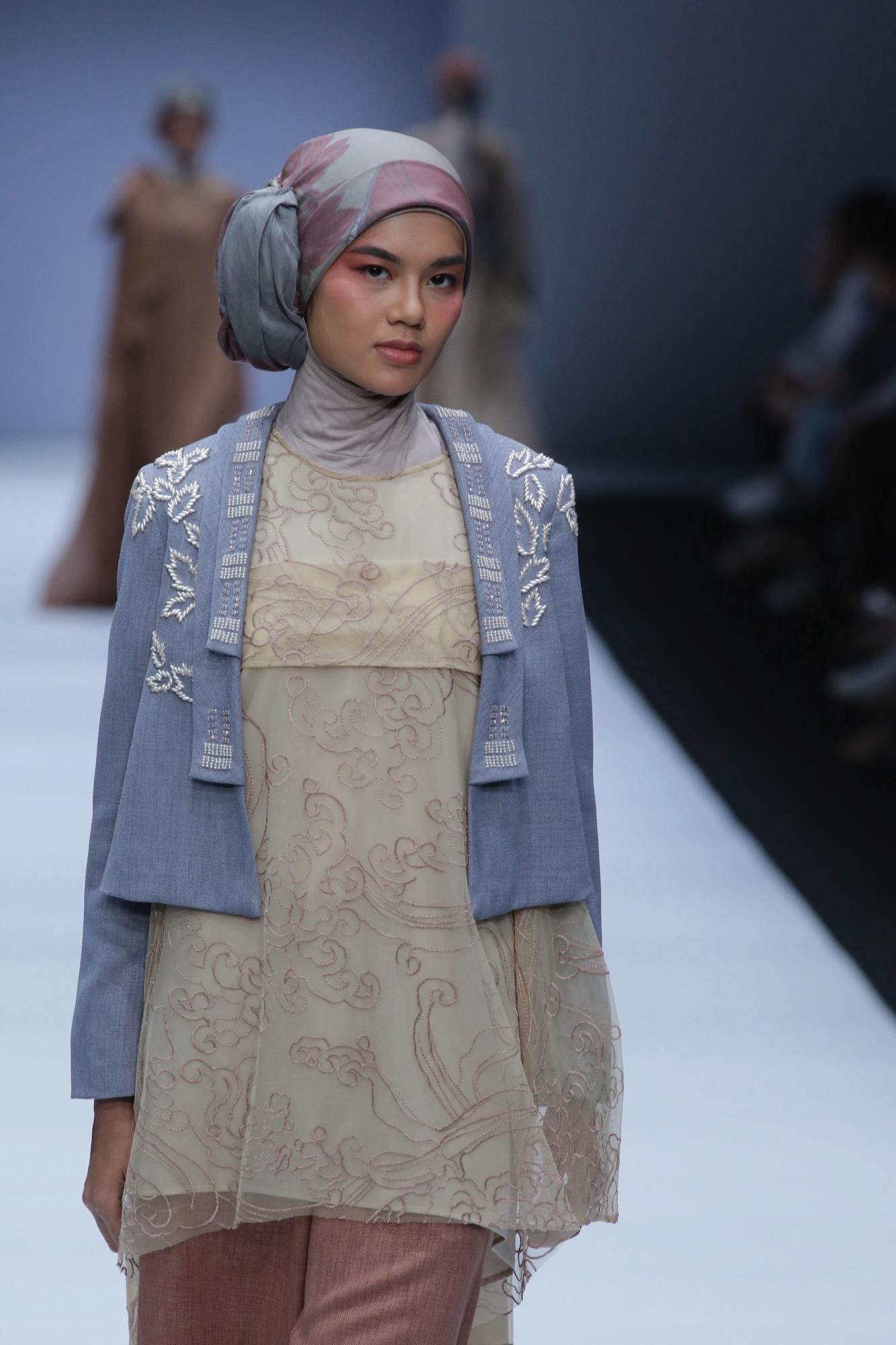 Wanita asia dengan model rambut hijab side bun dengan jaket denim – Jakarta Fashion Week 2019