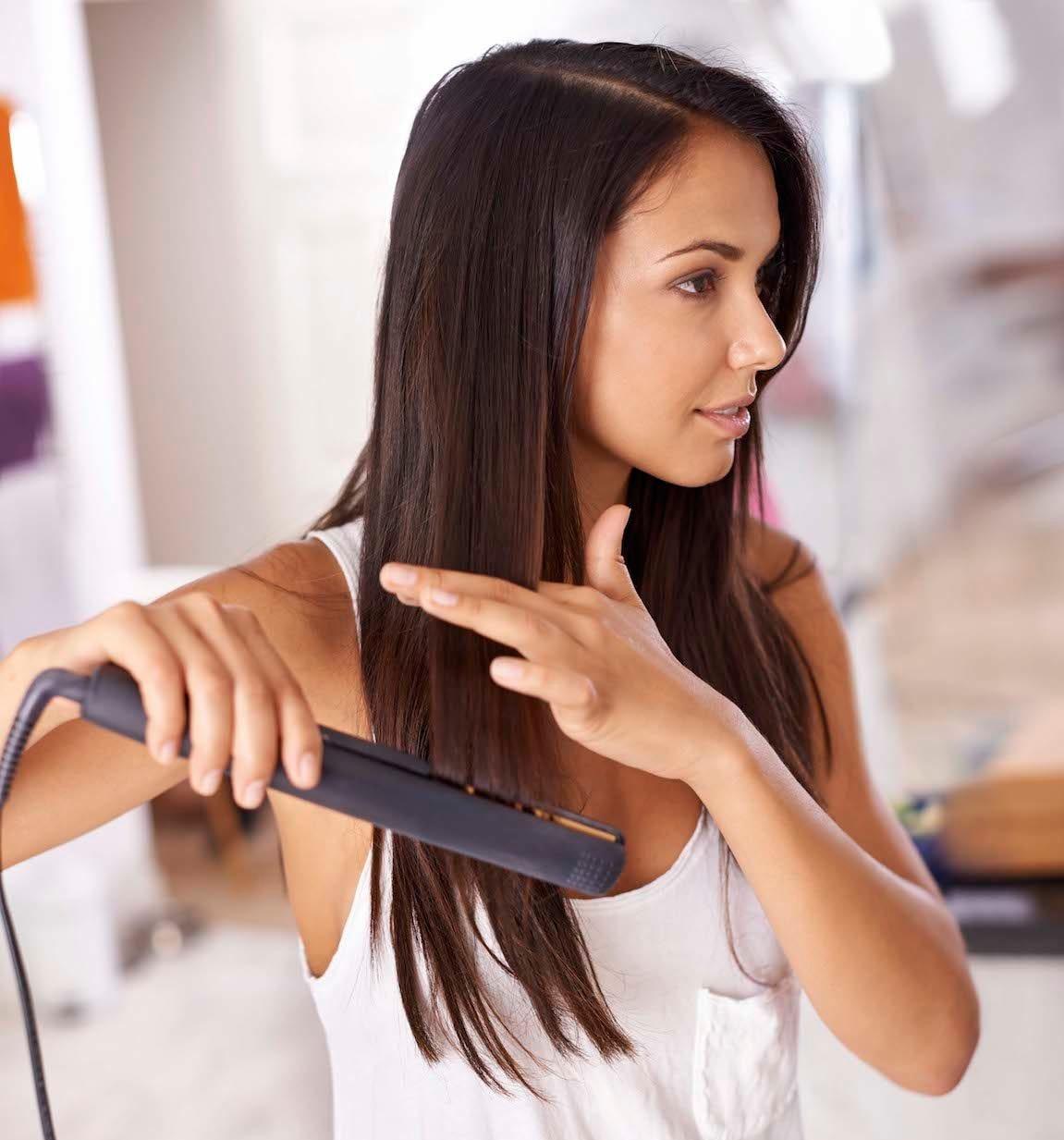 Perempuan kaukasia sedang menggunakan flat iron