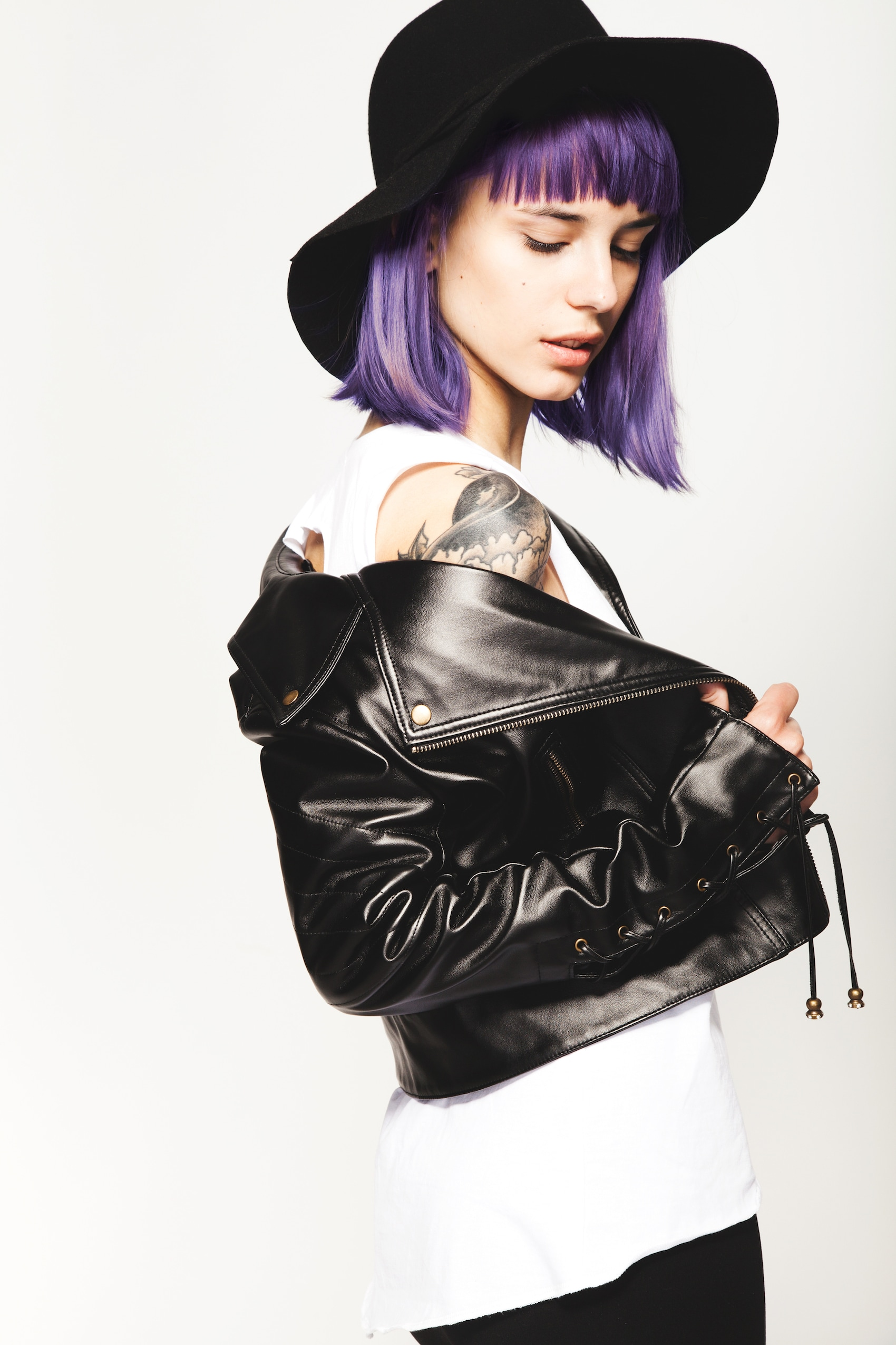 Wanita kaukasia dengan rambut warna ungu menggunakan topi warna hitam dan jaket kulit