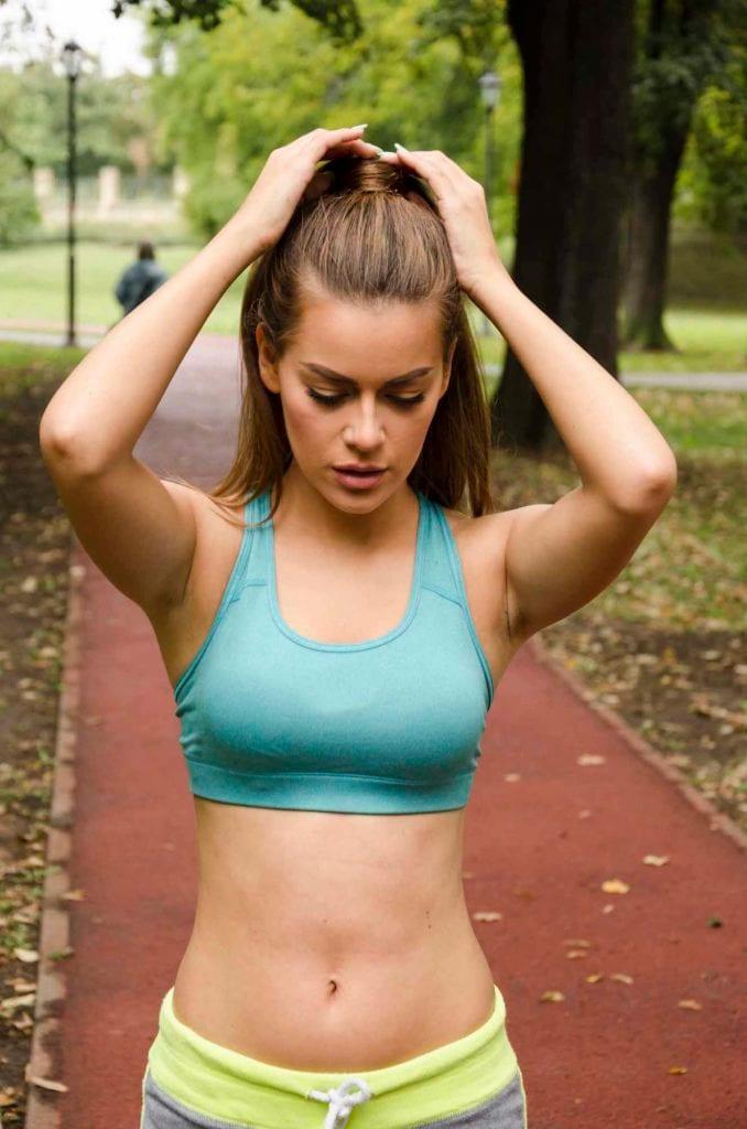 Gaya rambut sporty dengan model rambut wrapped ponytail.