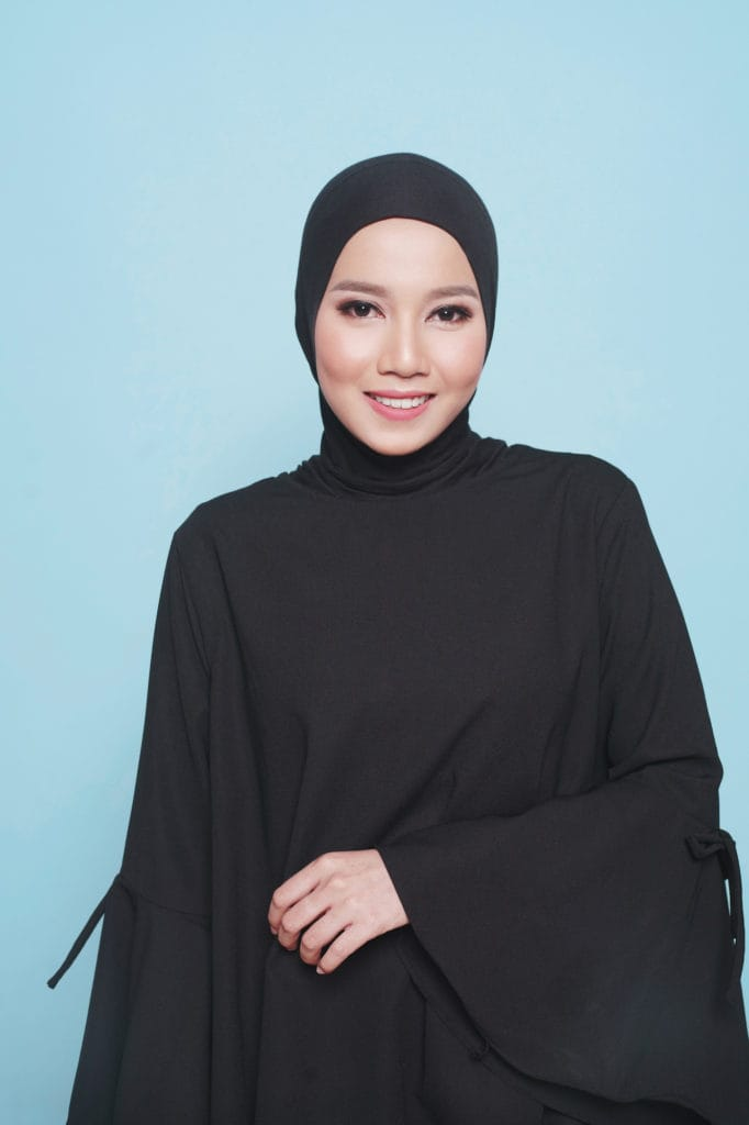Wanita asia dengan gaya hijab paris menggunakan ciput hitam.