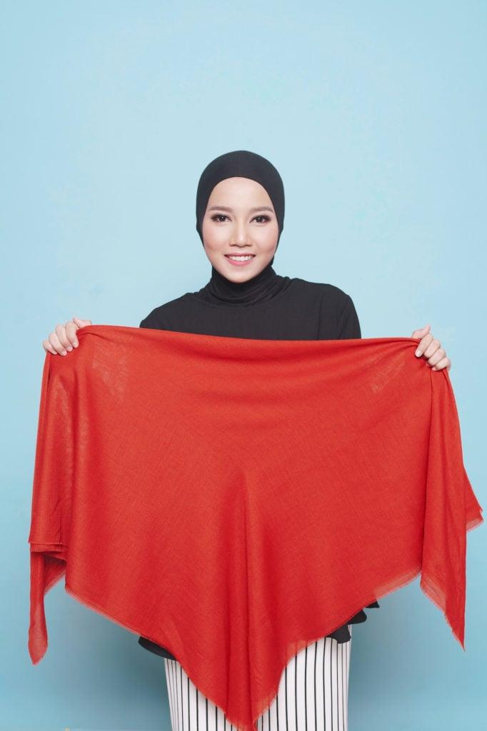 Wanita asia dengan gaya hijab paris warna merah melipat hijabnya menjadi segitiga