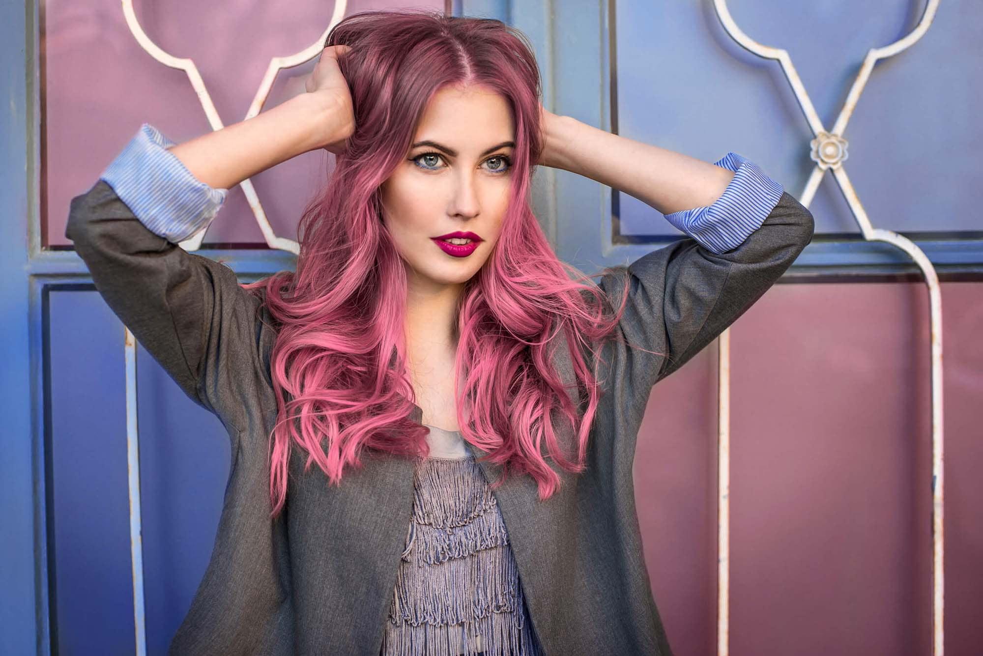 Warna rambut deep rosy pink pada rambut keriting panjang.