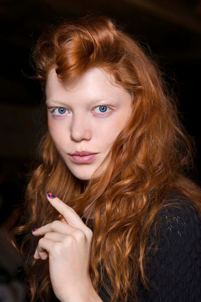Wanita kaukasia dengan rambut panjang keriting warna auburn terang