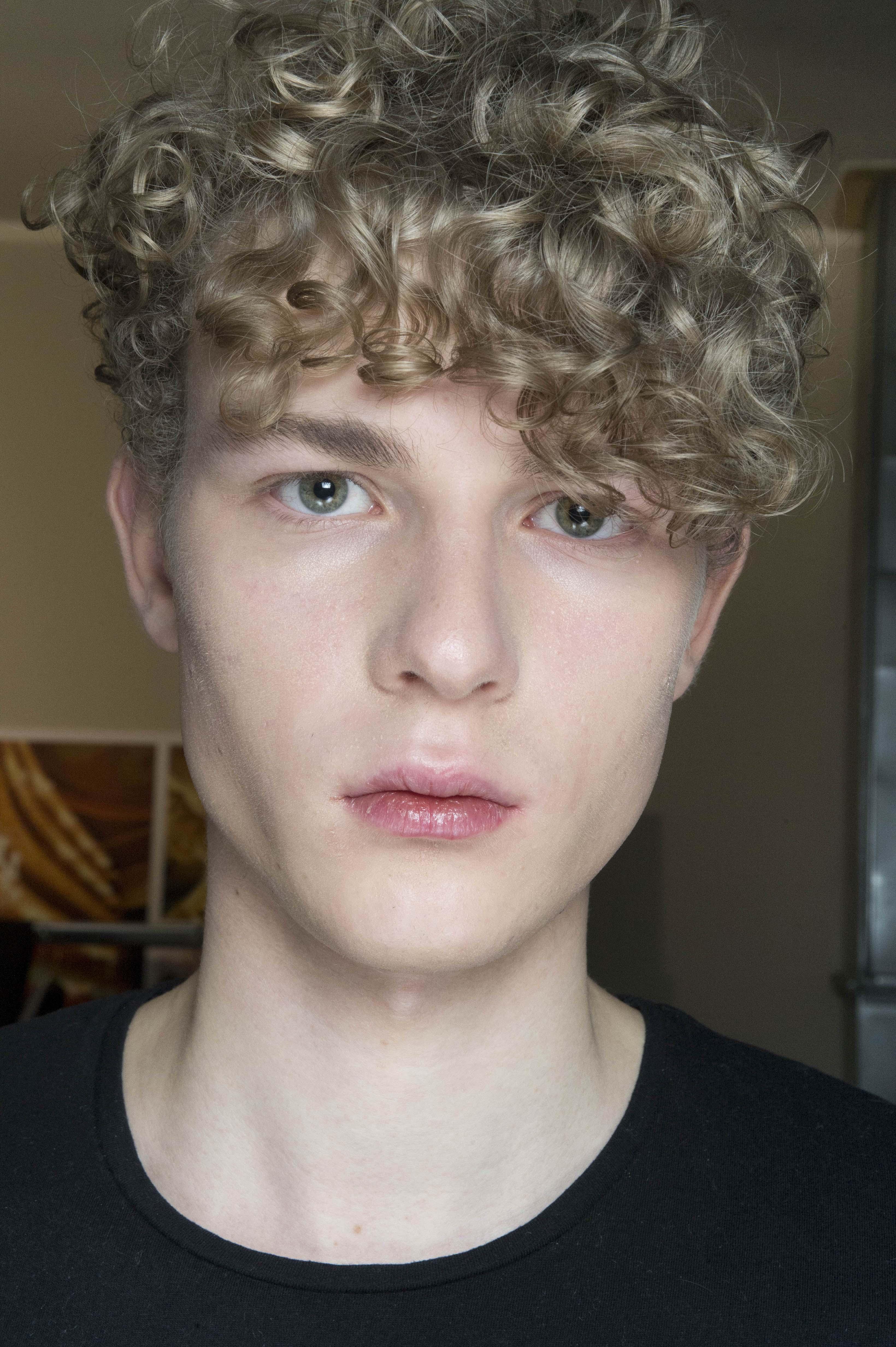Pria dengan model rambut curly undercut.