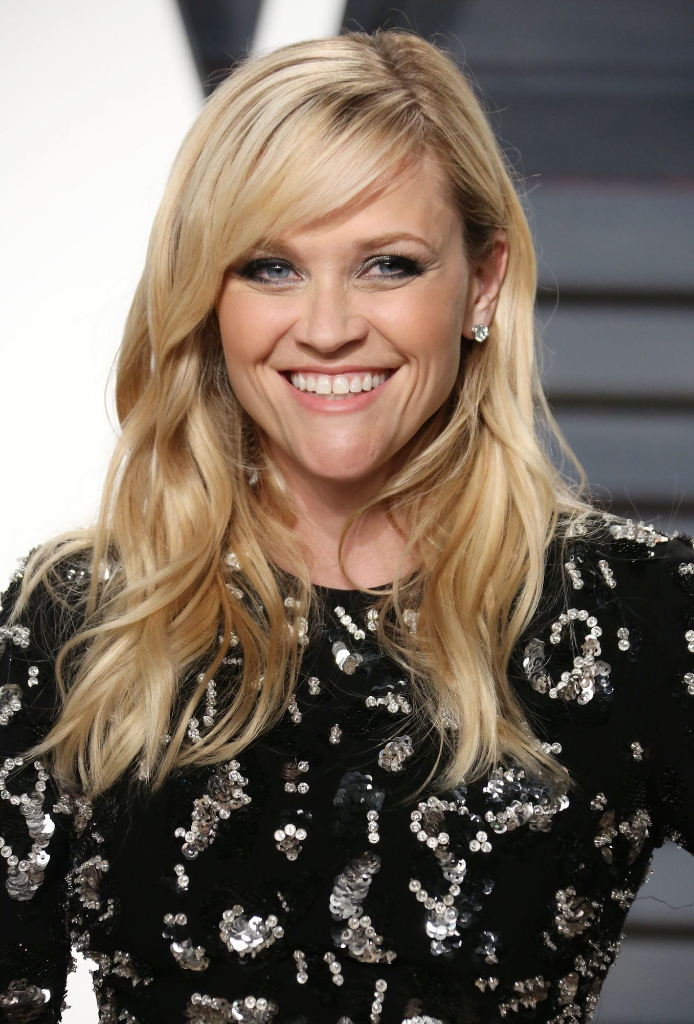 Reese Witherspoon potongan rambut layer panjang poni samping.