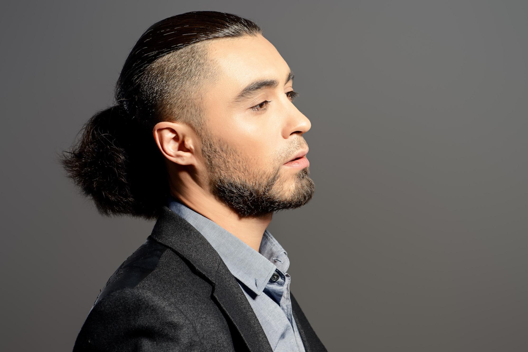 Gaya rambut pria tipis dengan model rambut undercut man bun.