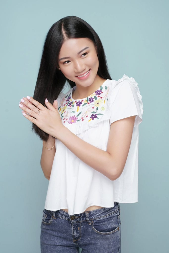 Wanita Asia dengan rambut panjang lurus sedang memakai vitamin rambut