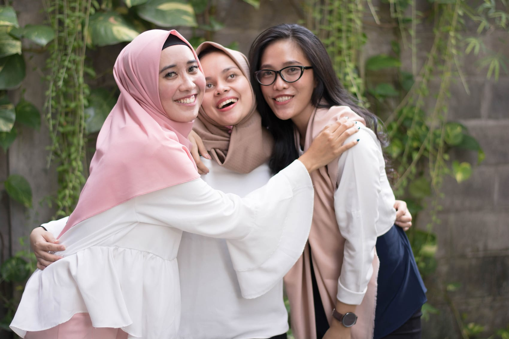 Tiga wanita asia dengan dua hijab dan satu tanpa hijab tersenyum ke kamera
