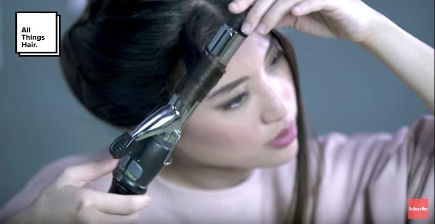 Keriting rambut menggunakan curling iron.