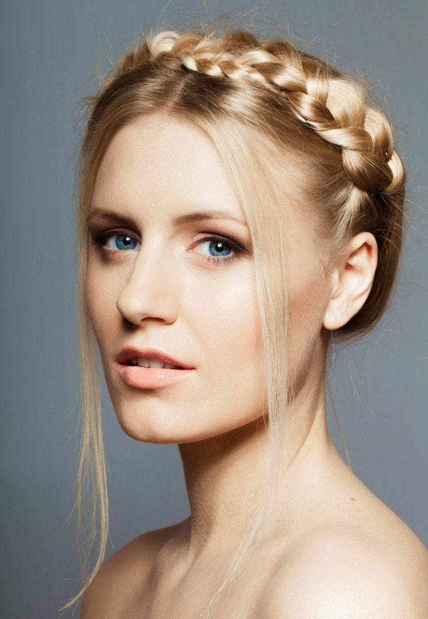 Model rambut yunani dengan gaya milkmaid braid belah tengah.