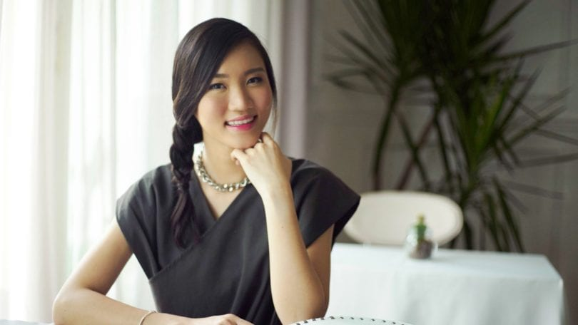 Wanita asia duduk di kafe dengan baju hitam.