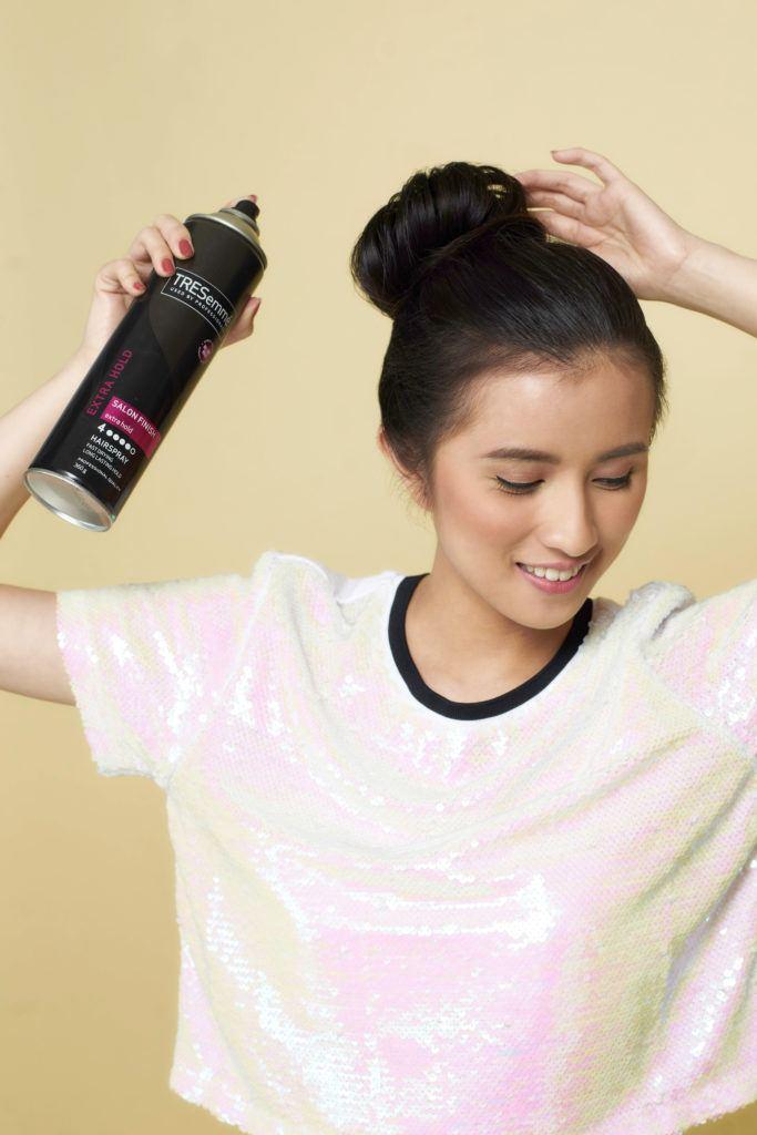 Wanita asia dengan warna rambut warna hitam dengan model rambut ballerina bun sedang menyemprotkan hairspray pada ballerina bun
