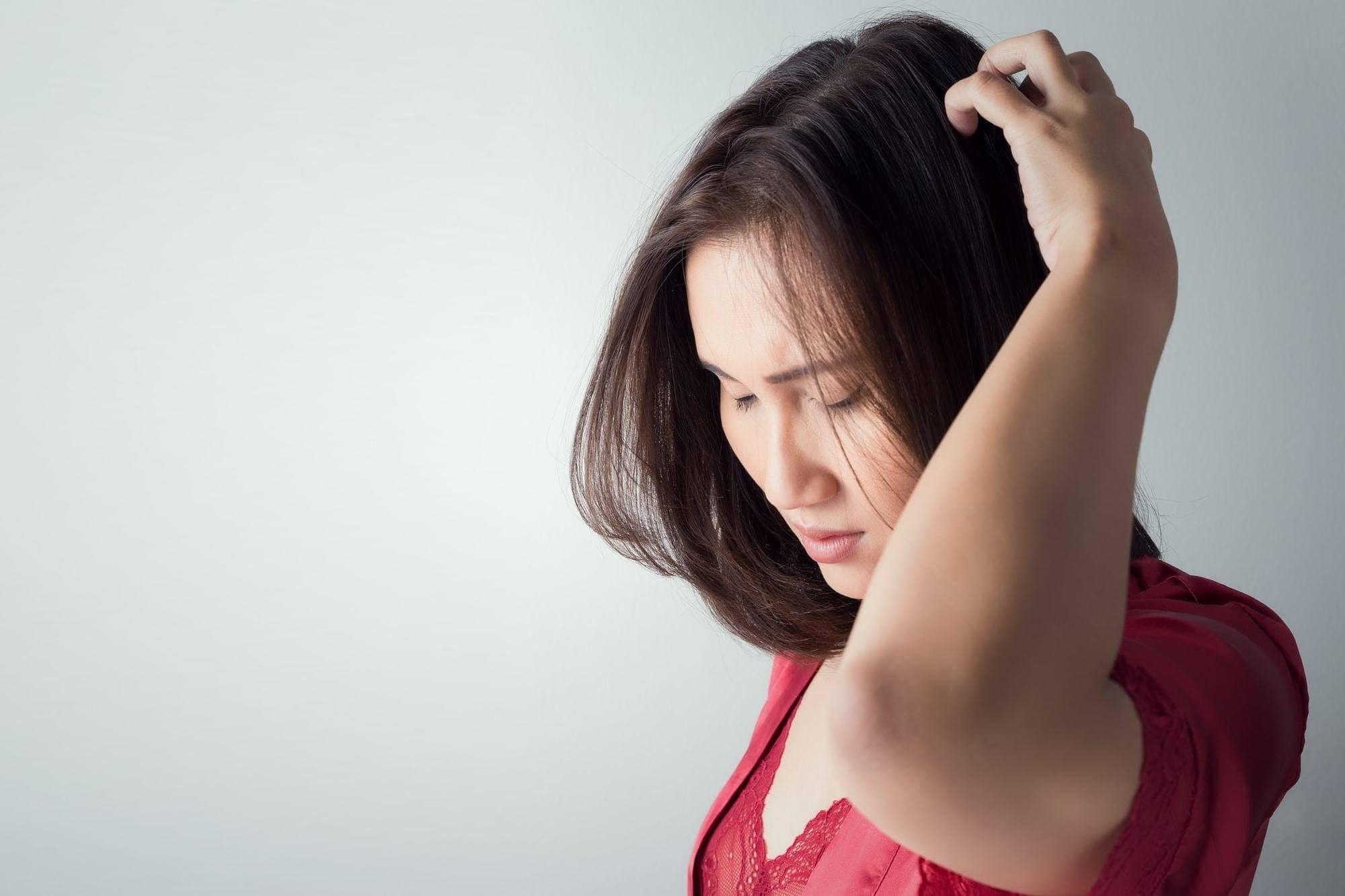 Wanita asia dengan baju merah menyentuh kulit kepala.