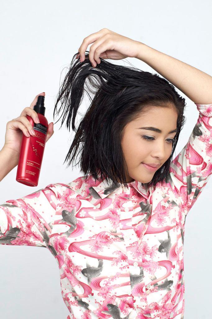 Wanita asia dengan rambut hitam menyemprotkan heat protection spray
