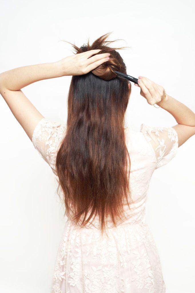 Wanita asia menata gaya rambut braided updo.