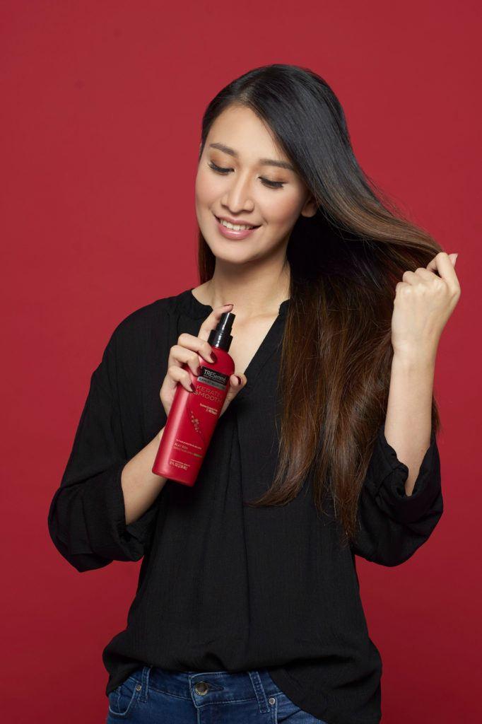 Wanita asia menyemprotkan heat protection spray ke batang rambutnya