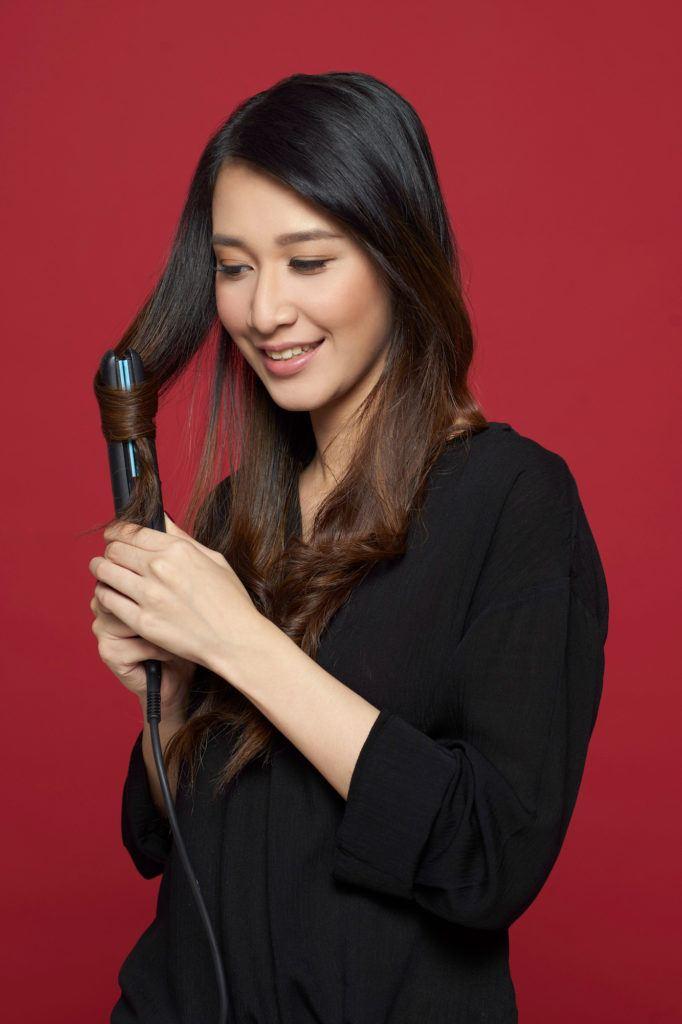 Wanita asia mengeriting rambut hitamnya.