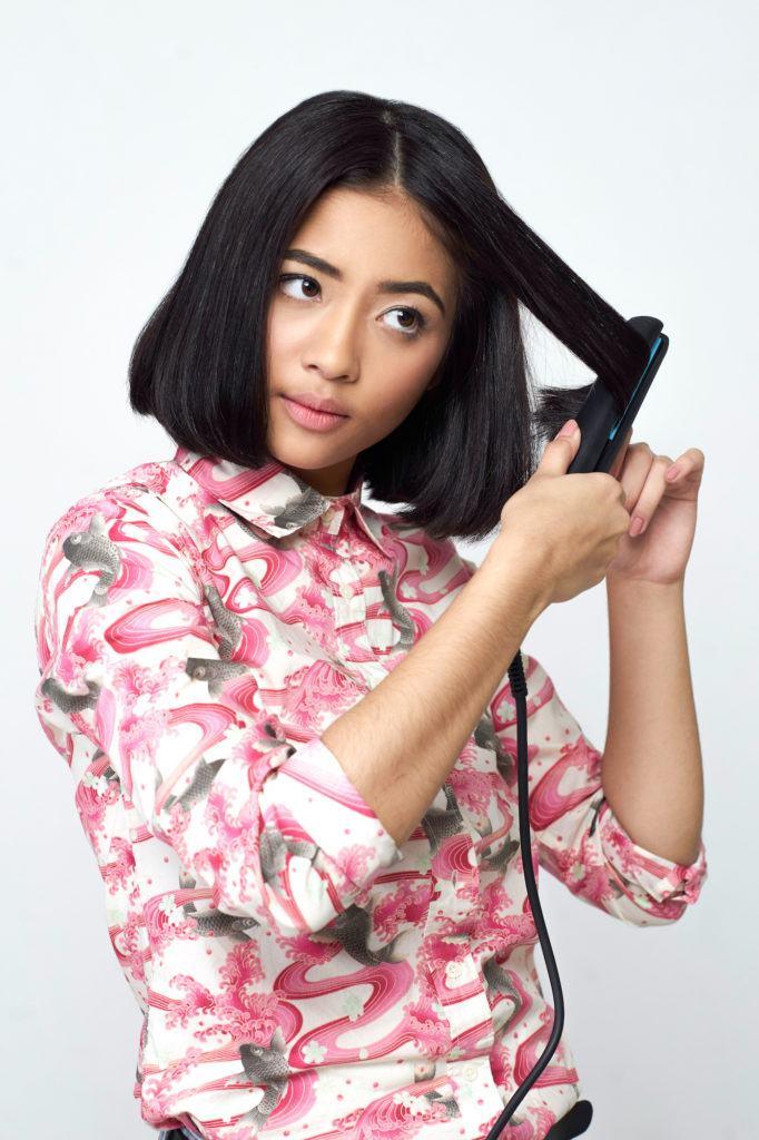 Wanita Asia sedang mencatok rambut bob pendek.