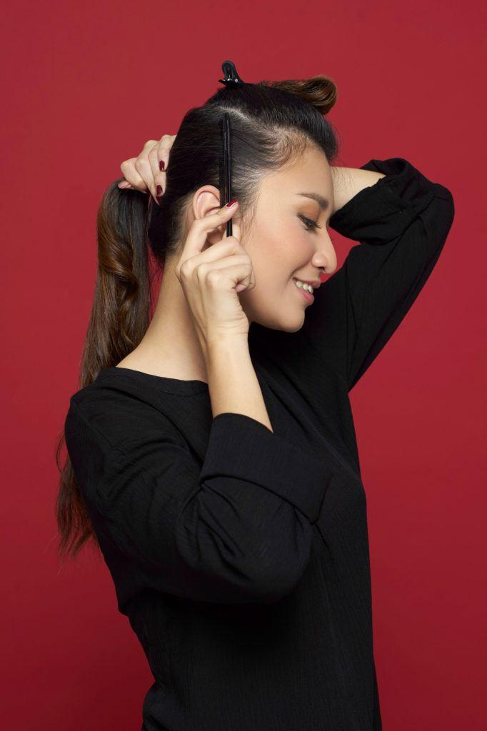 Wanita asia membagi rambutnya dengan jepit rambut.