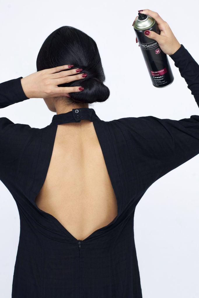Wanita asia menyemprotkan hairspray pada rambut gaya chignon.
