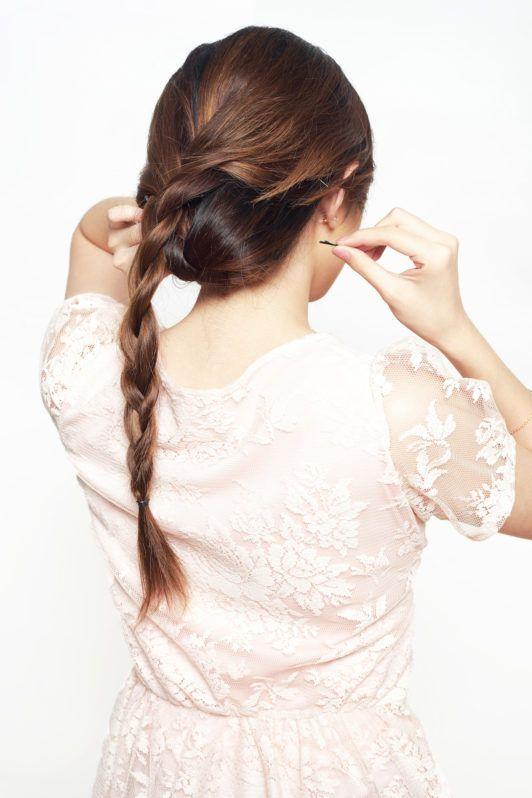 Wanita asia membuat gaya braided updo.