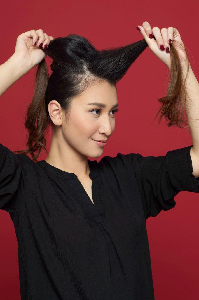 Wanita asia warna rambut hitam dengan atasan hitam membagi dua bagian rambutnya