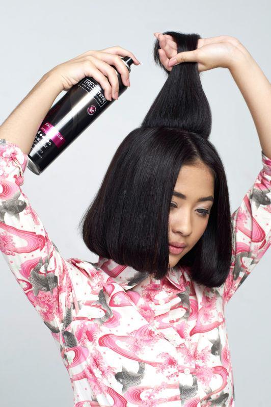 Wanita asia dengan rambut pendek hitam menyemprotkan hairspray pada rambut.