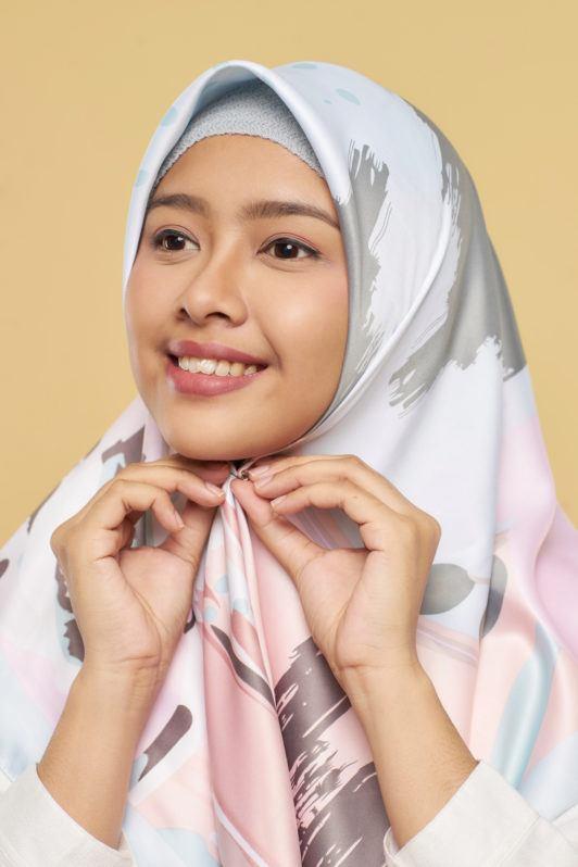 Wanita asia dengan hijab warna pastel sedang menata hijab