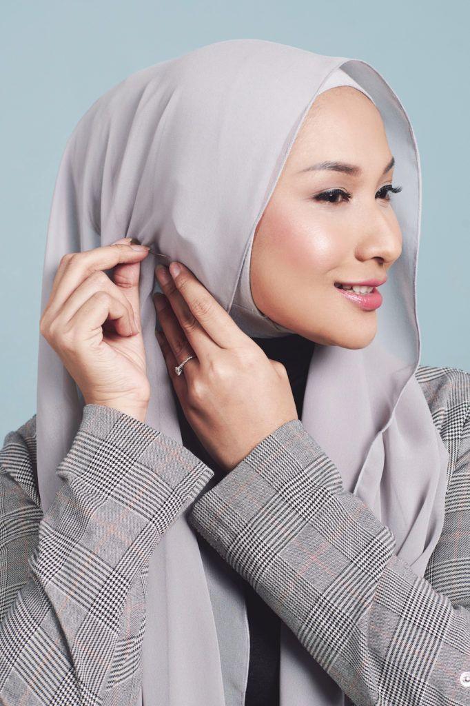 Wanita dengan hijab abu-abu menggunakan jarum pentul