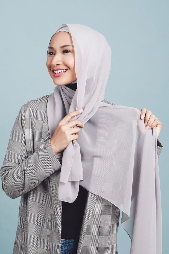 Wanita asia menata hijabnya dengan disilang