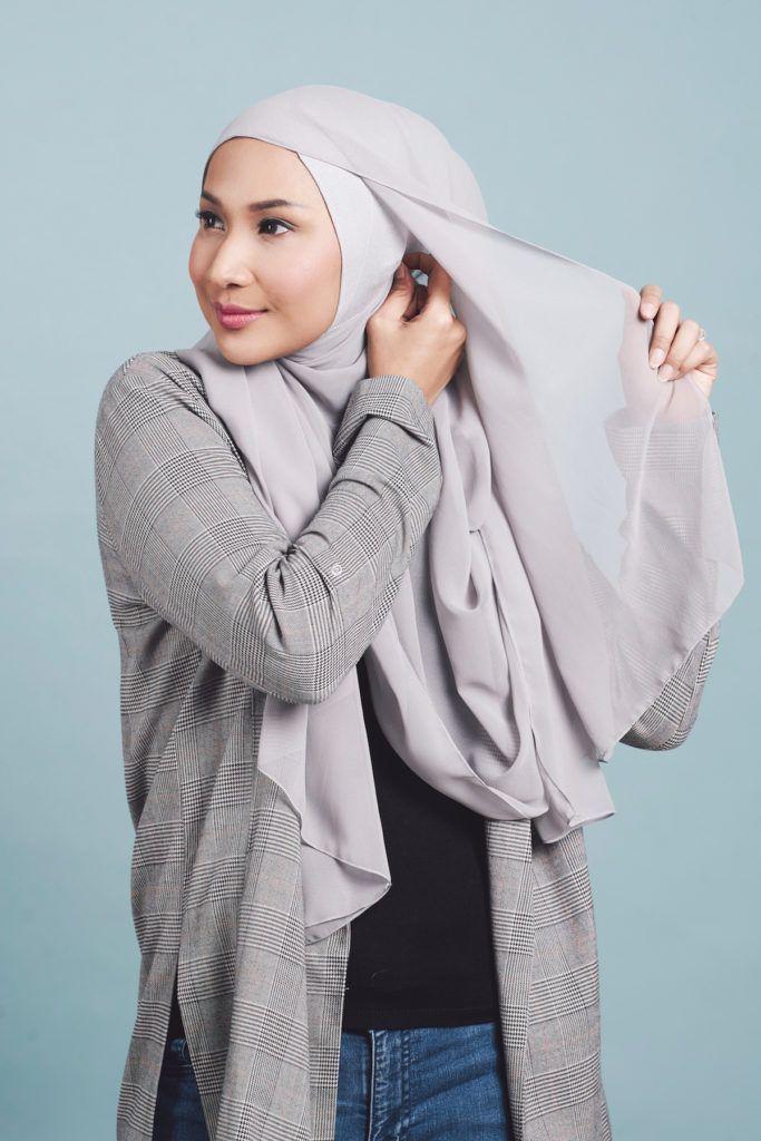 Wanita asia menyematkan jarum pentul pada hijabnya