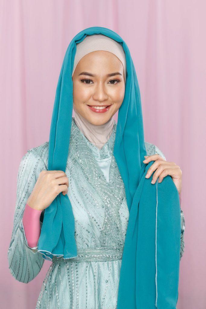 Wanita memasangkan hijab pashmina hijau di kepalanya