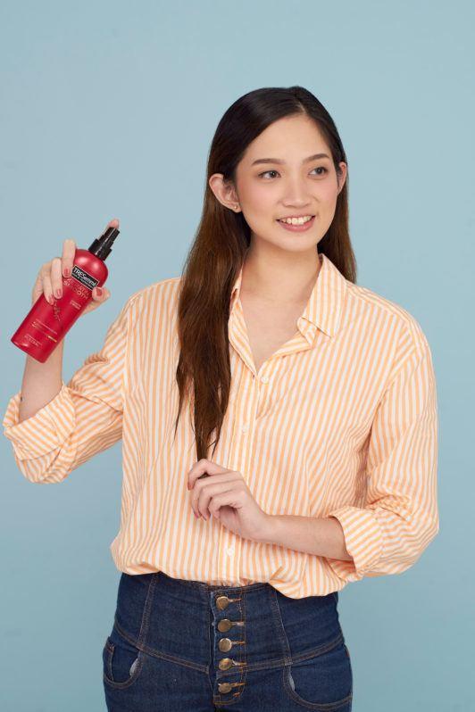 Wanita asia dengan rambut panjang menyemprotkan spray rambut - cara membuat rambut terlihat tebal