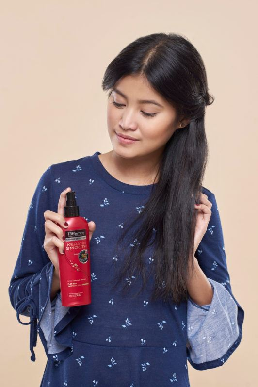 Wanita asia dengan rambut hitam menyemprotkan TRESemme Heat Protection Spray - half crown braid