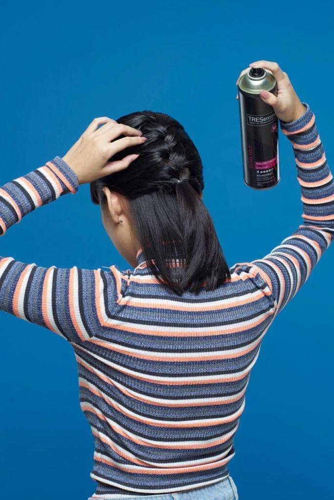Wanita asia dengan rambut pendek hitam menyemprotkan hairspray pada kepang rambut