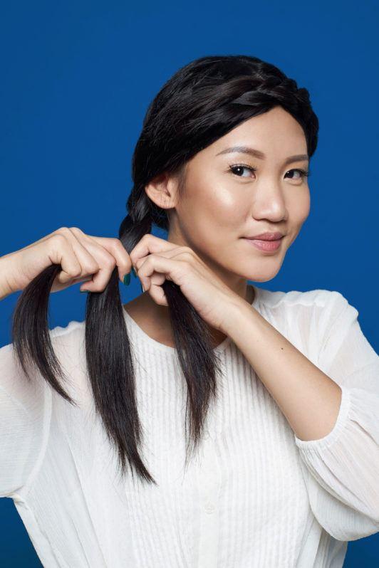 Wanita asia dengan rambut hitam panjang menata rambut gaya crown braid.