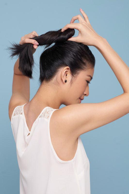 Wanita asia membentuk ponytail untuk gaya french braid bun warna rambut hitam