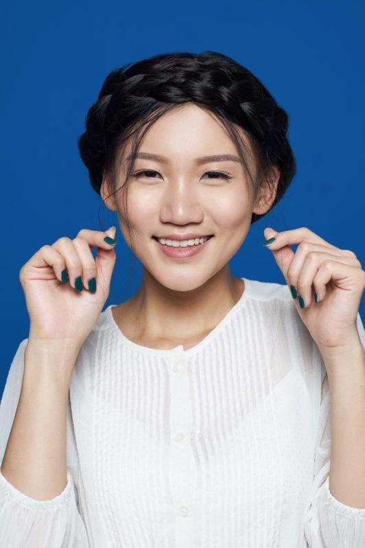 Wanita asia menata rambut gaya crown braid.