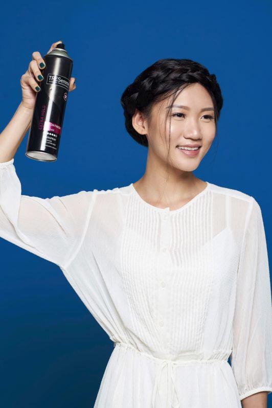 Crown braid – wanita asia menyemprotkan hairspray pada rambut hitamnya.