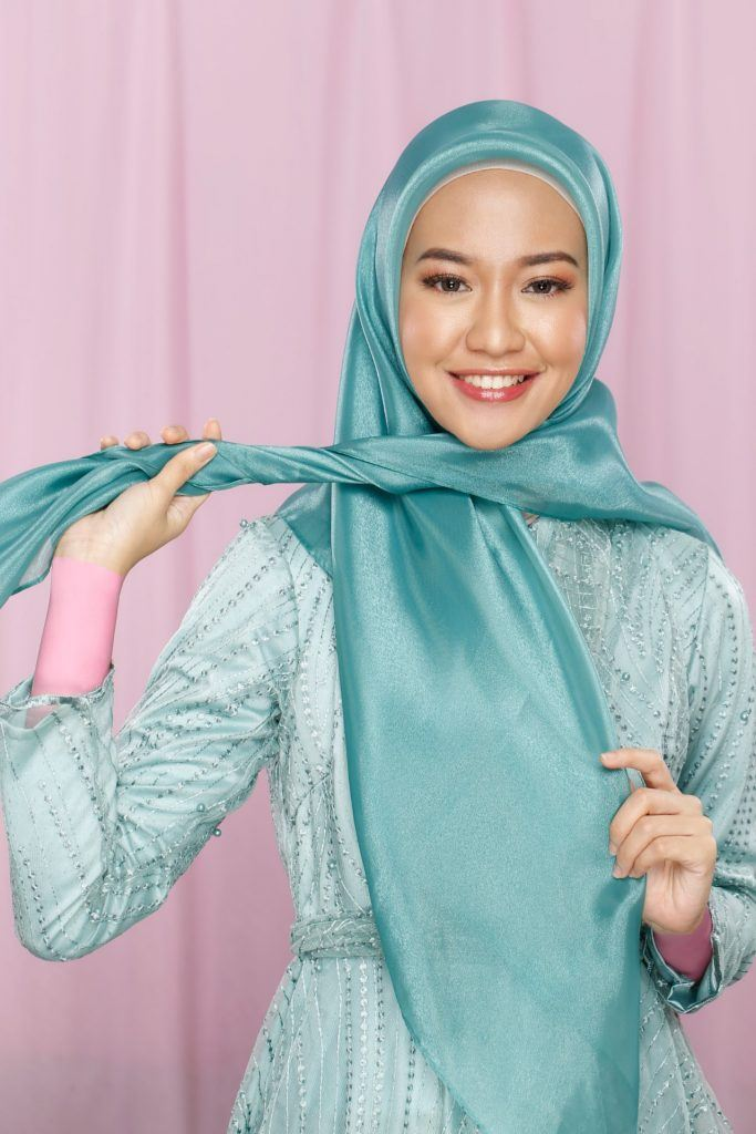 Wanita menunjukkan tutorial hijab pesta memakai jilbab organza.
