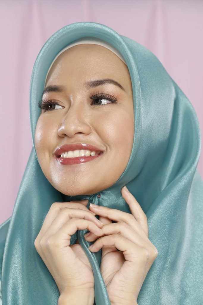 Wanita merekatkan hijab organza di kepalanya