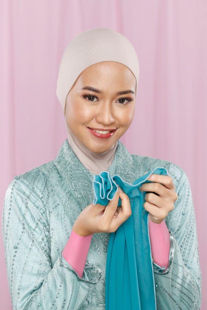 Wanita memilin hijab berwarna hijau