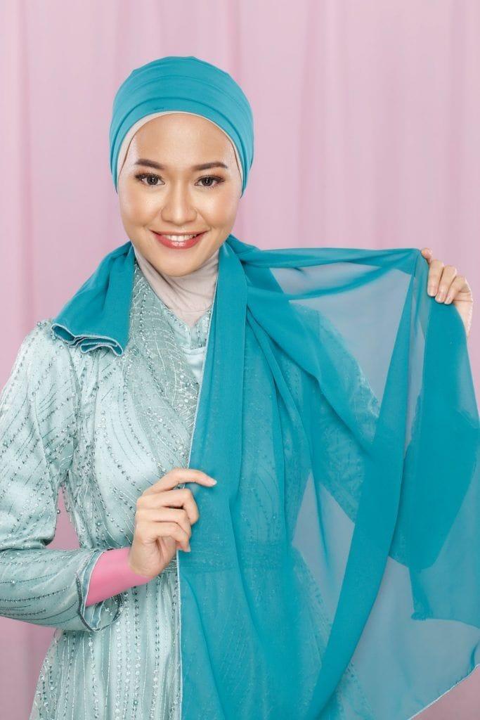 Wanita memperlihatkan tutorial hijab pesta.
