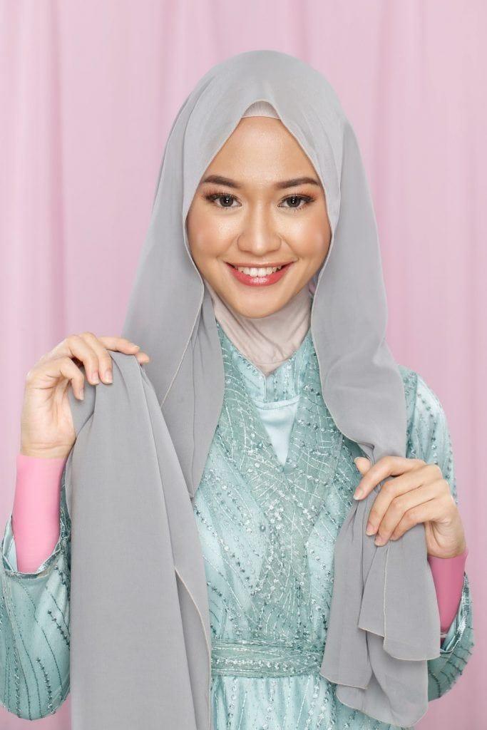 Wanita Asia memasangkan hijab sifon di kepalanya
