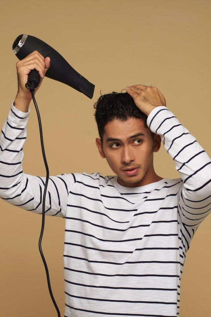 Pria Asia mengeringkan rambut dengan hairdryer