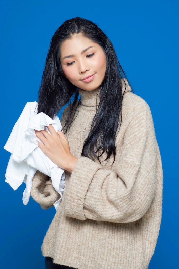 Wanita asia dengan rambut panjang hitam mengeringkan rambut dengan kaus katun – cara mengatasi rambut kusut