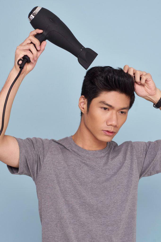 Pria asia dengan rambut hitam menata gaya quiff dengan menggunakan hairdryer
